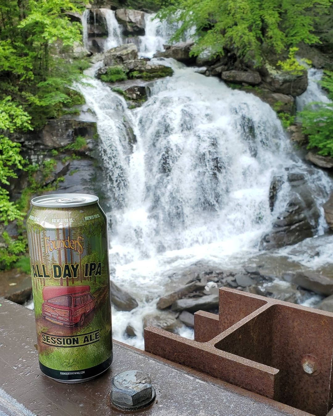 A large can of All Day IPA in front of a waterfall.