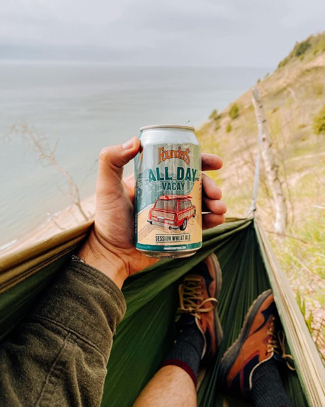 A hand holding a can of All Day Vacay in a hammock on the sand.