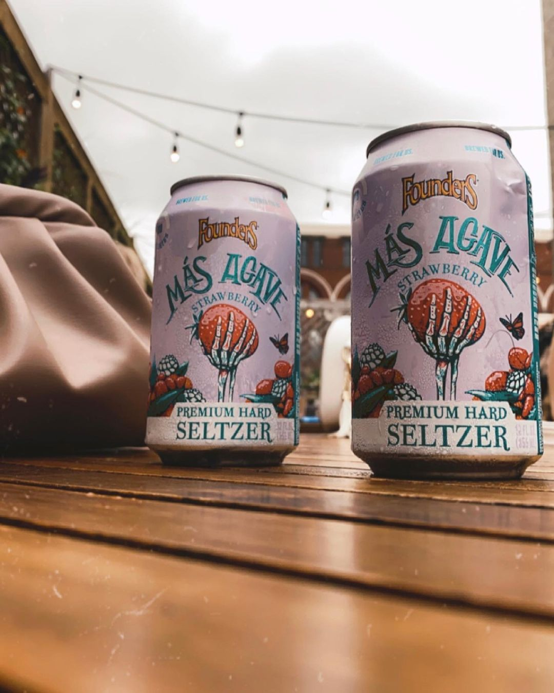 Two cans of mas agave premium hard seltzer strawberry in a beer garden.