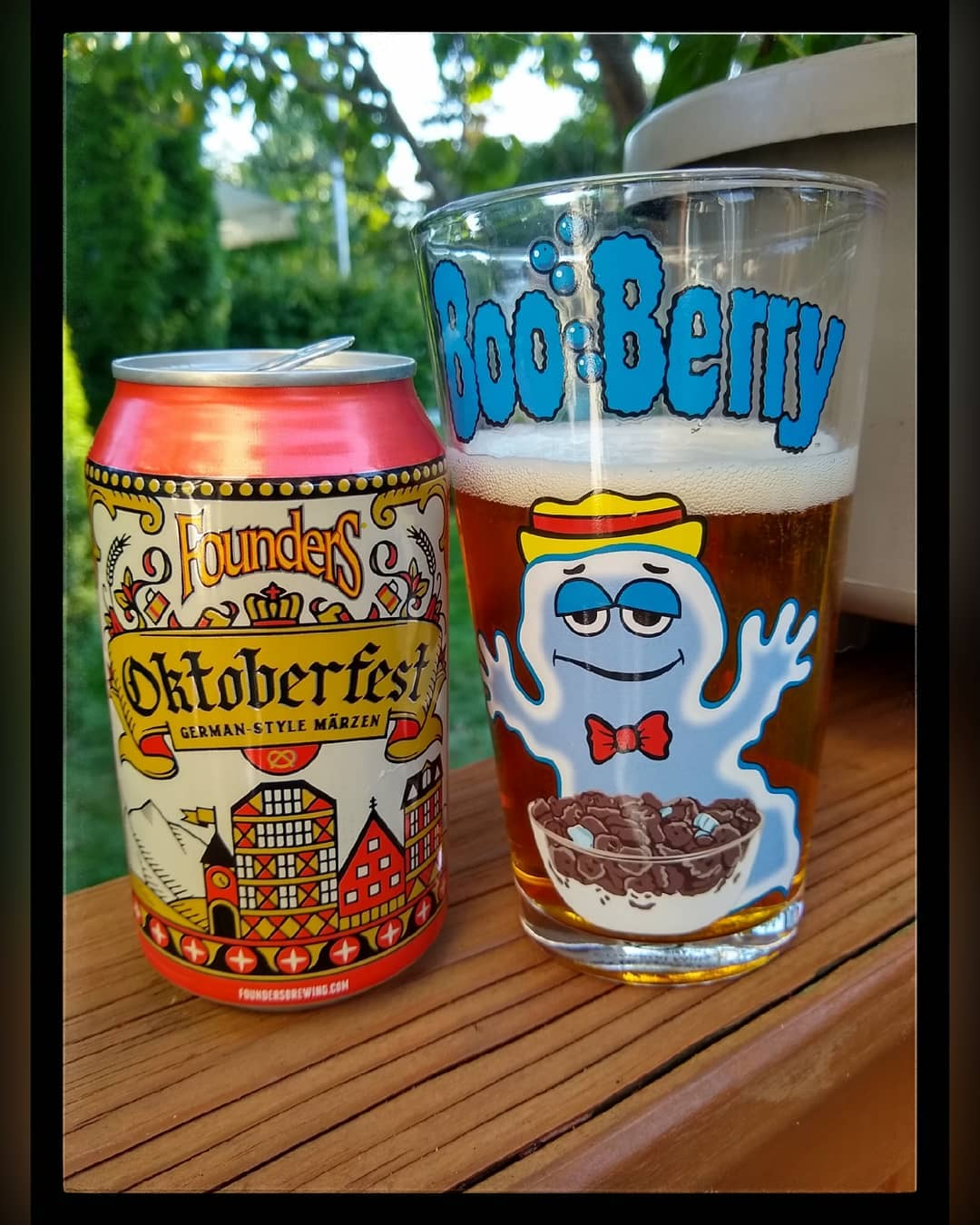 A pint glass with a pour branded with Boo Berry cereal next to a can of Oktoberfest.