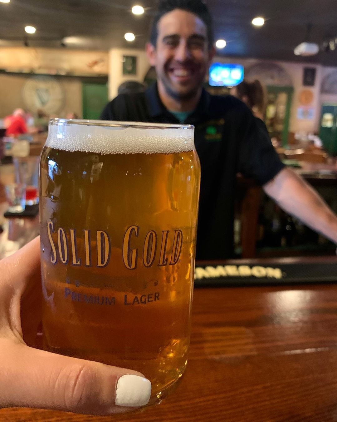 A hand holding a branded pint glass of Solid Gold in front of a bartender.