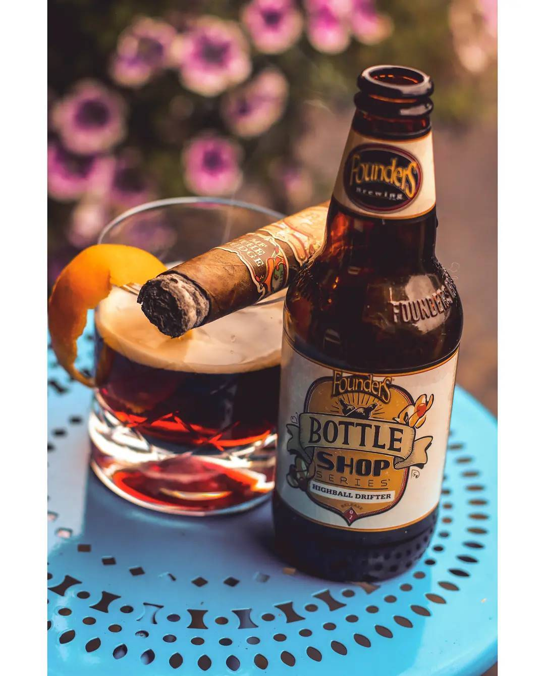 A bottle of Highball Drifter next to a pour and a cigar in front of some flowers.