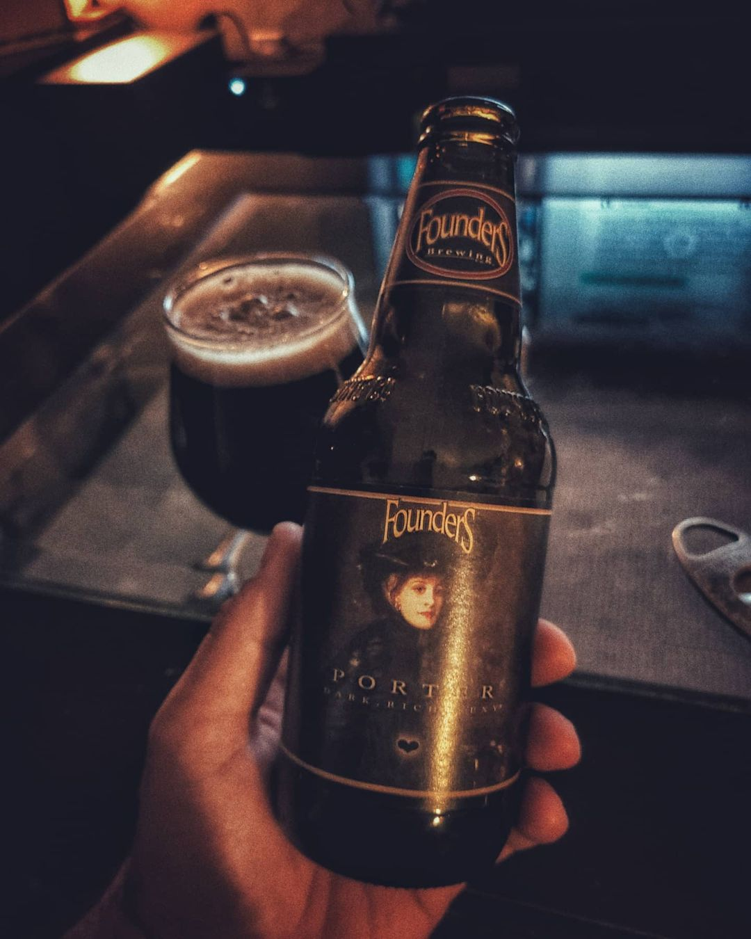 A hand holding a bottle of Porter in front of a cigar.